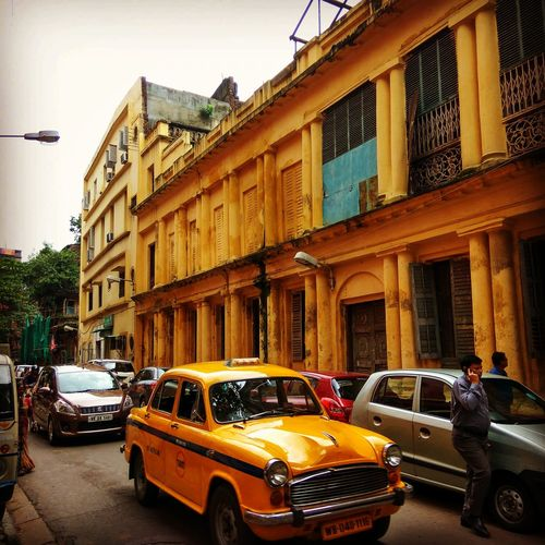 Yellow Car Land Vehicle Car Land Vehicle Mode Of Transport Transportation Architecture Building Exterior Built Structure Street Parking In A Row Traffic Stationary Window Old-fashioned City Parked History Day In Front Of Rush Hour City KolkataStreets Colonial Cities