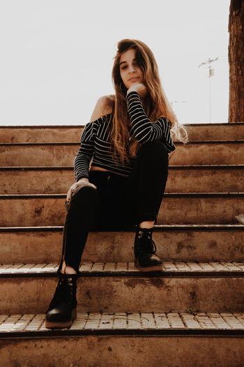 Portrait of girl sitting on steps against sky