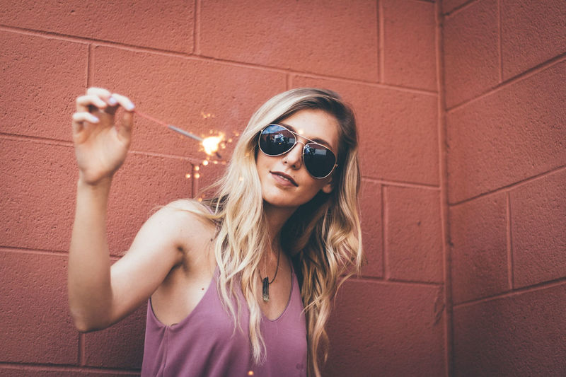 Celebrate the 4th. Sunglasses One Person Portrait Adult One Woman Only People Smiling Only Women Young Adult Summer Adults Only Fun Pets Looking At Camera Leisure Activity Happiness Outdoors Standing Cheerful Blond Hair Individuality Women Long Hair Adult One Young Woman Only