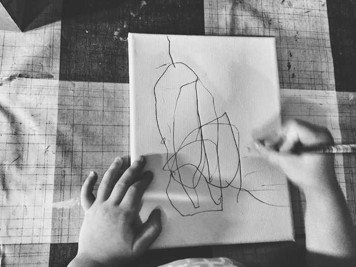 Cropped Hands Of Child Drawing On Paper