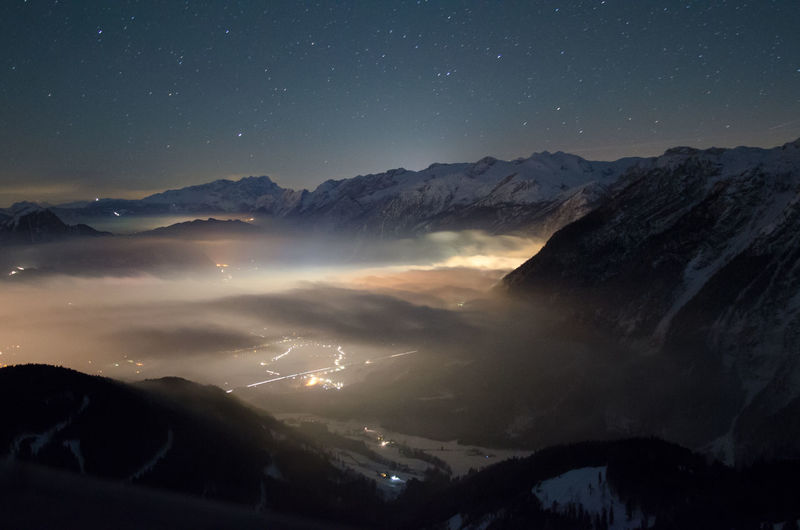 Scenic view of illuminated town covered with fog amidst snowcapped mountains