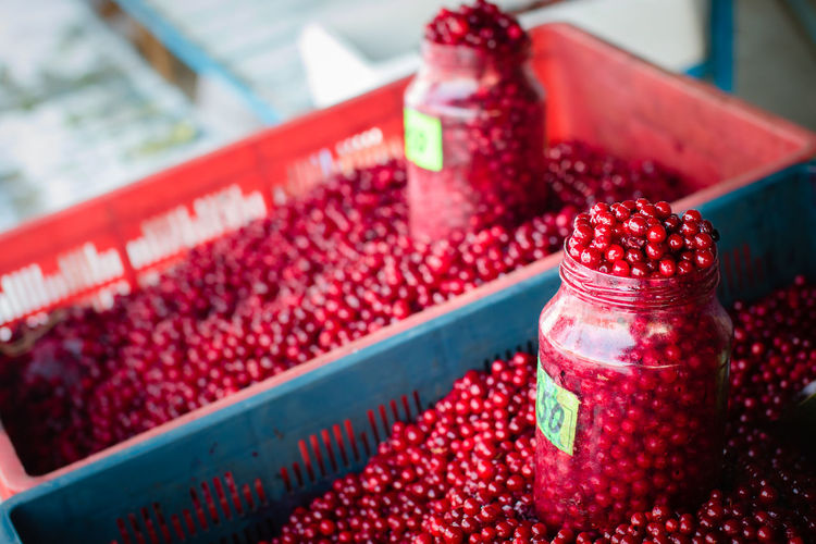 High angle view of cranberries in containers at market for sale