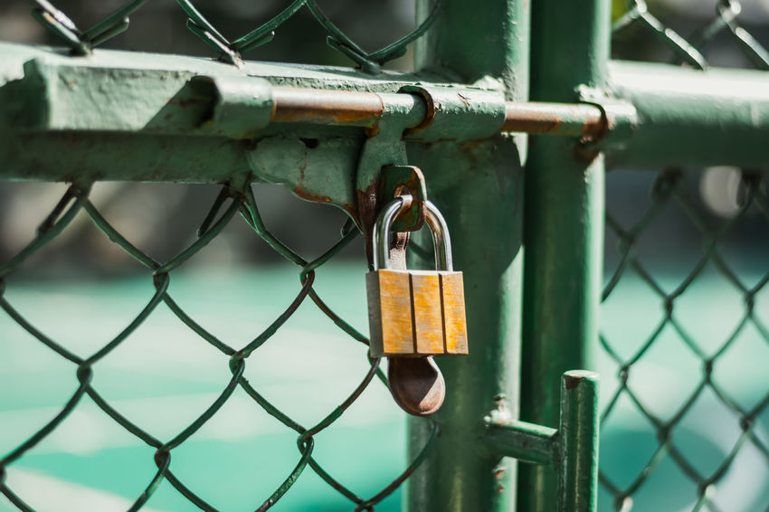 Close up of old rusty lock on green fence.Locks on the net.Blurred background. Gate Locks Wall Backgrounds Border Chain Chainlink Fence Close-up Day Fence Hanging Hope Lock Love Love Lock Luck Metal No People Outdoors Padlock Protection Railing Safe Safety Security