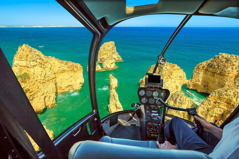 Helicopter cockpit interior flying on scenic landscape of boat trip between cliffs and natural rock formations of Ponta da Piedade. Scenic flight above Lagos, Algarve, Portugal skyline, Atlantic Ocean Cockpit View Cockpit Interior Flight Scenic Flight Flying Aerial View Panorama Skyline Beach Sea Seascape Portugal Rock Formation Douro River Portugal Serra Do Pilar Vila Nova De Gaia Oporto City Sunset Window Azenhas Do Mar Ponta Da Piedade Marinha Beach Natural Arch Helicopter Water Transportation Nature Mode Of Transportation Day Sky Land Scenics - Nature One Person Air Vehicle Vehicle Interior Horizon Beauty In Nature Travel Outdoors Airplane Horizon Over Water