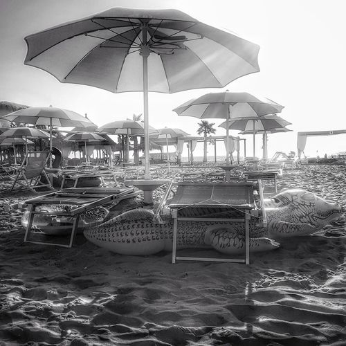 Deck chairs and parasols on beach against sky