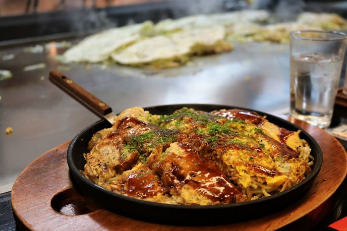 Okonomiyaki, Hiroshima's signature dish, is a savoury pancake filled with cabbage, noodles, and other fillings of your choice. Comfort Food Cooking Dinner Hot Hot Plate Japanese  Japanese Food Japanese Traditional Japanese Style Close-up Day Focus On Foreground Food Food And Drink Freshness Healthy Eating Hiroshima Hot Food Indoors  Meat No People Okonomiyaki Plate Ready-to-eat Table Be. Ready. Food Stories Shades Of Winter Modern Workplace Culture Adventures In The City Modern Hospitality #urbanana: The Urban Playground