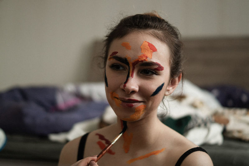 Close-up of young woman applying body paint