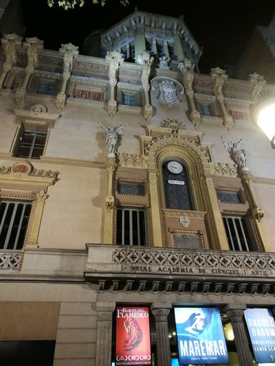 Ciné Barcelona, Spain Noche City Illuminated History Architecture Building Exterior Built Structure Statue Sculpted Female Likeness Angel Carving Flaming Torch Human Representation