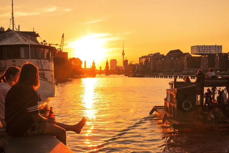 People sitting on boat in city during sunset