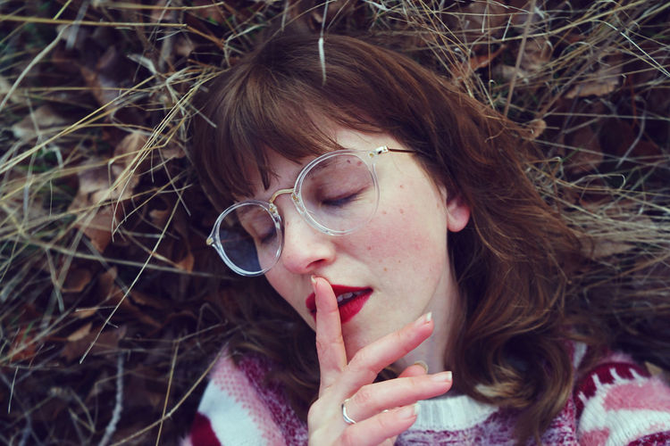 Close-Up Of Young Woman With Finger On Lips Lying At Field