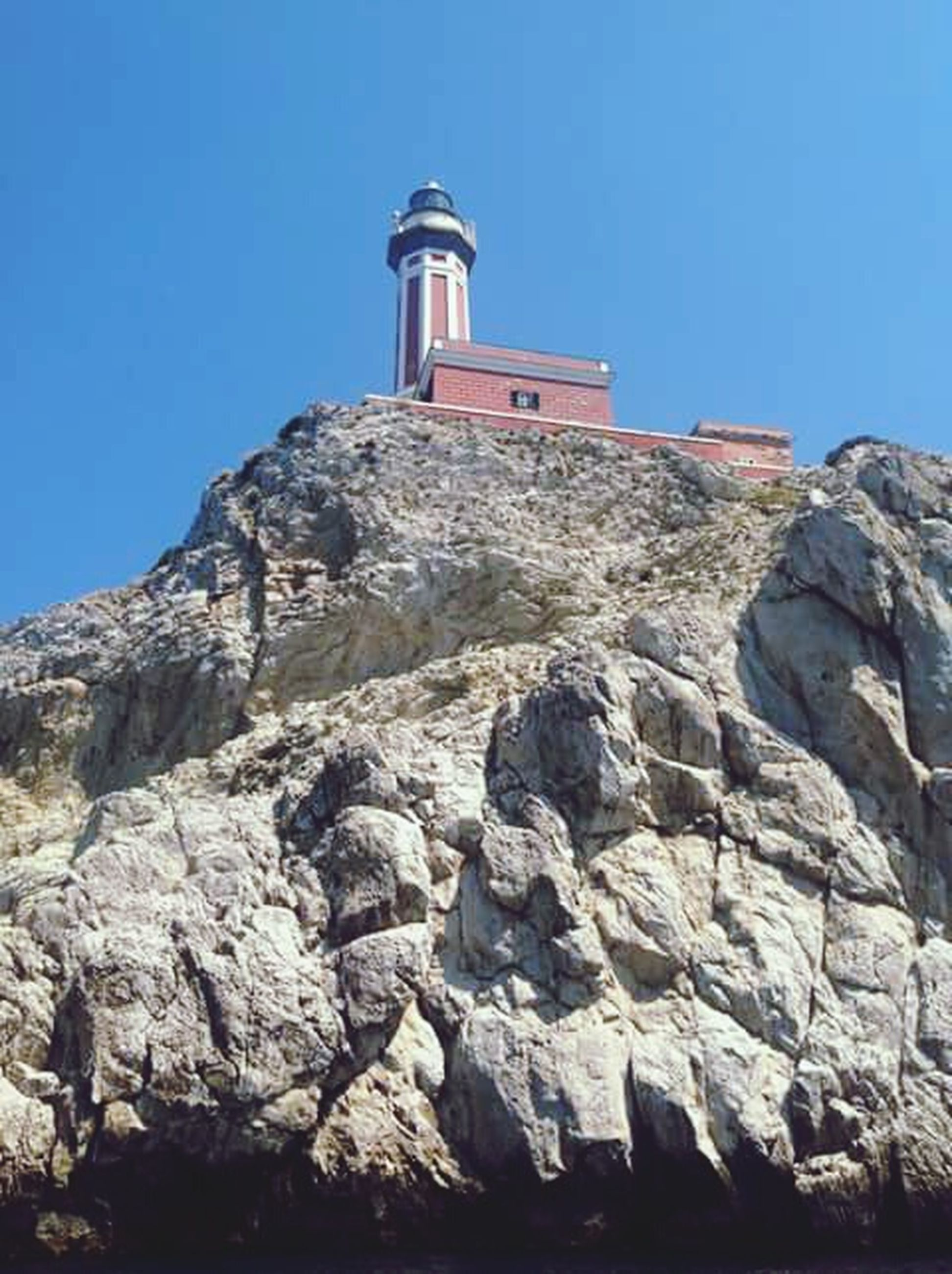 clear sky, built structure, architecture, building exterior, low angle view, blue, lighthouse, rock - object, copy space, guidance, sunlight, rock formation, stone wall, day, tower, rock, outdoors, nature, no people, mountain