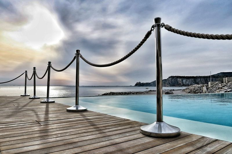 Railing on pier at poolside against cloudy sky