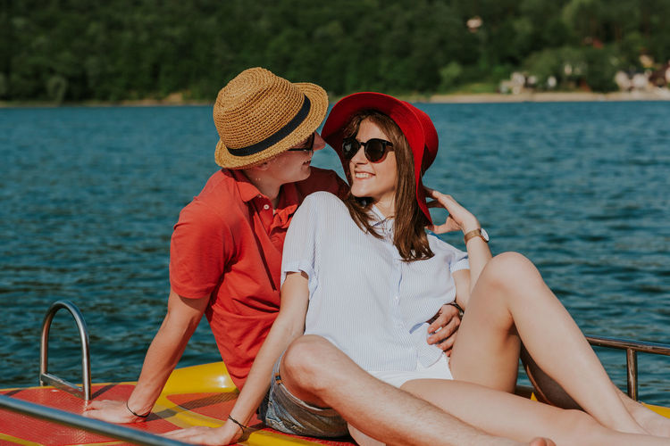 Cheerful man and woman having fun while boating. Portrait of couple in love enjoying being together on pedal boat on warm sunny day. Boating Couple Holiday Hot Day Love Summertime Vacations Young Boat Boyfriend Caucasian Feet Girlfriend Lake Outdoors Pedalo Relax Resting River Sea Summer Sunglasses Sunhat Two People Water