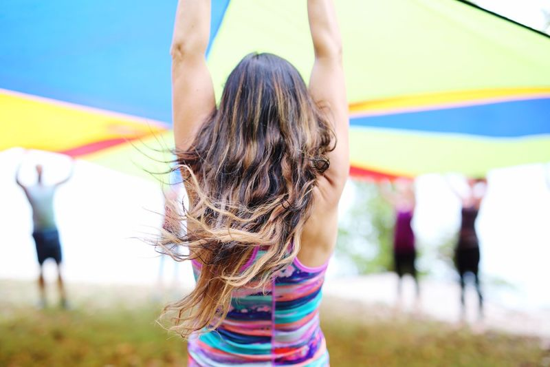 Rear View Of Woman Holding Parachute On Field