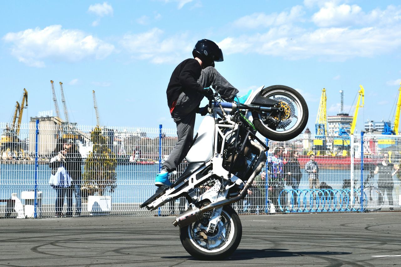 bicycle, transportation, mode of transport, land vehicle, real people, day, skill, riding, helmet, stunt, sport, outdoors, sky, motorcycle, cloud - sky, men, bmx cycling, leisure activity, headwear, lifestyles, sports helmet, city, one person, extreme sports, biker, cycling helmet, people