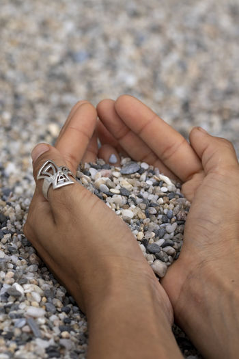 Low section of person holding pebbles on rock