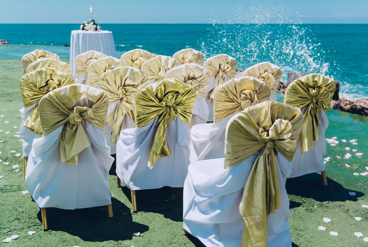 Row of wedding white chairs decorated with golden bows on the beach Bright Celebration Chair In A Row Romantic Sunlight Wedding Wedding Reception Beach Beauty In Nature Celebration Event Ceremony Chairs Horizon Over Water No People Nobody Outdoors Row Sea Sunny Day Turquoise Water Water Wedding Ceremony Wedding Chairs Wedding Day