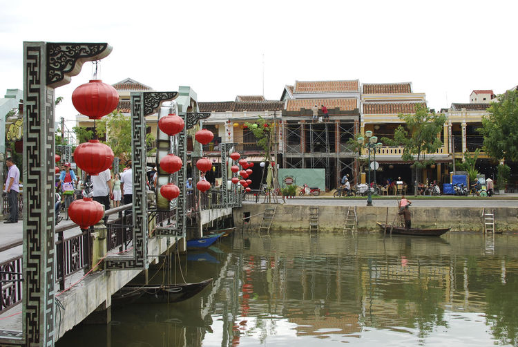 River Crossing | Hoi An, Vietnam Architecture Bridge Bridge - Man Made Structure Building Exterior Built Structure City City Life Clear Sky Connection Culture Day Footbridge Hoi An Hoi An, Vietnam Lantern Outdoors Railing Red Reflection Riverbank Sky Vacations Vietnam Water Waterfront