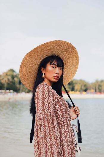 Portrait of young woman wearing hat standing at beach against sky