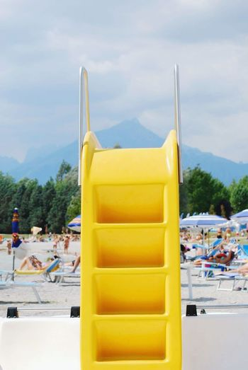 Yellow slide at beach against sky