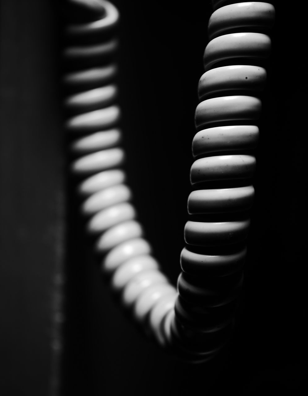 close-up, striped, spiral, no people, indoors, metal, electricity, cable, dark, focus on foreground, pattern, technology, connection, selective focus, single object, black color, still life, day, midsection, equipment, black background, electrical component, power supply