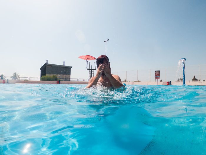 Man swimming in pool by sea against clear sky