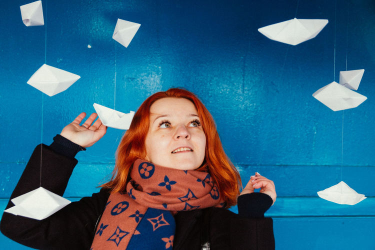 Smiling woman looking at paper boats hanging against blue wall
