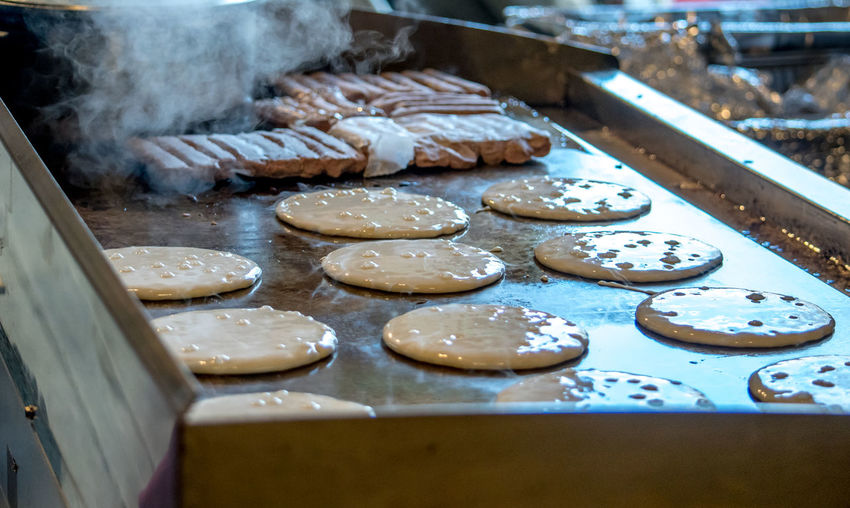 Hot golden pancakes cook on a metal griddle at a pancake breakfast