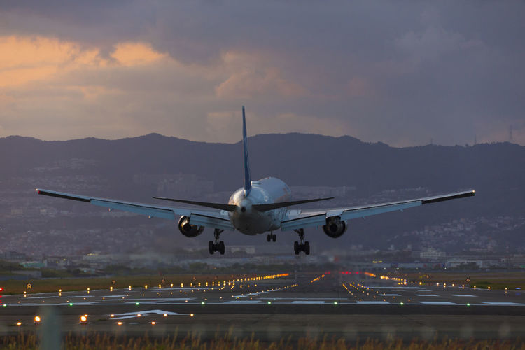 Airplane on runway against sky at sunset