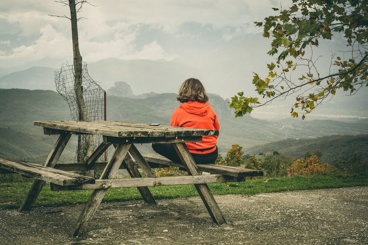 Rear view of man sitting on picnic table against mountains
