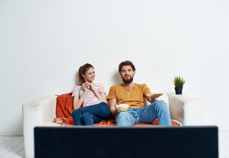 Friends looking away while sitting on sofa at home