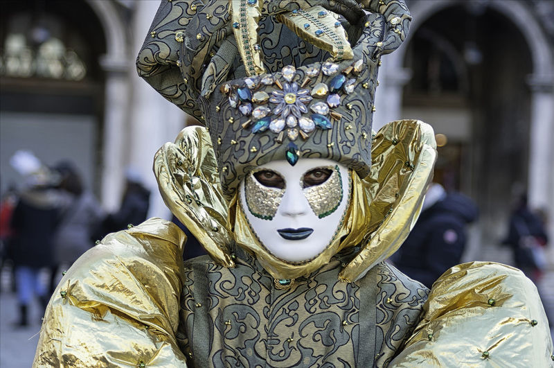 Portrait of a man wearing a white and green mask and a golden dress during the Venetian carnival party in San Marco square Gold Green Man Masque Tradition Venetian Carneval Carnival Colorful Costume Culture Disguise Dressing Festival Hide Italian Italy Mask Masquerade Outdoors Portrait San Marco Traditional Unrecognizable Venice