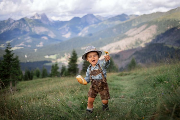 Portrait of boy holding food and flower on mountain