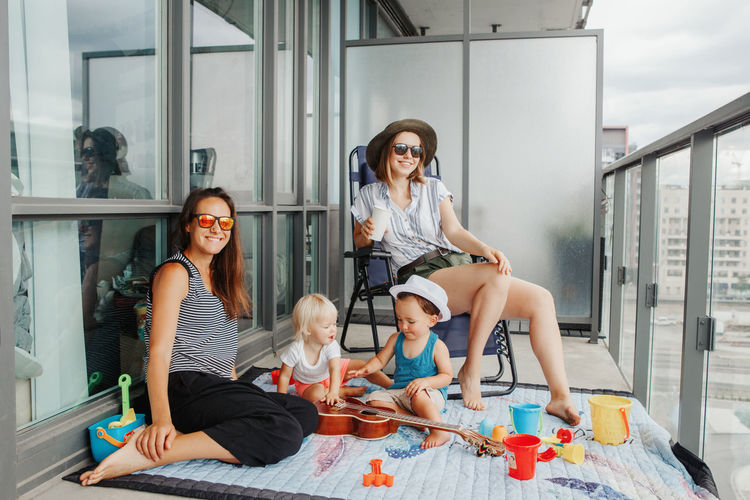 Young mothers spending time together with children babies on balcony at home. staycation
