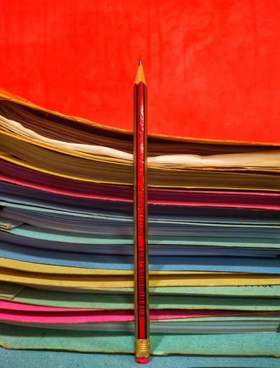 Close-up of multi colored pencils on table against wall