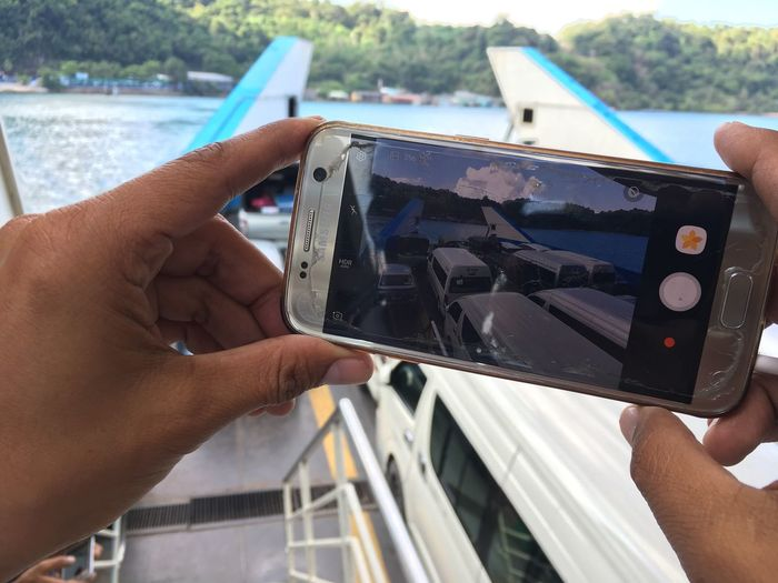 Picture in picture Transportation Minibuses Vans Cars Vehicles Boat Ferry Thailand Koh Chang Human Hand Human Body Part Human Finger Personal Perspective Holding Wireless Technology Photography Themes Close-up Photographing Mobile Phone Device Screen Day Outdoors