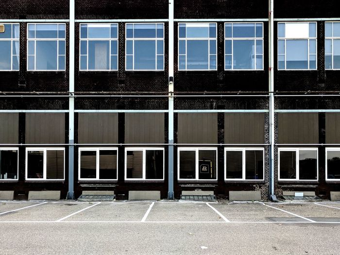 Windows of an industrial building and parking lot.