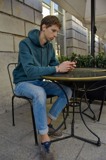 Shoot in Gent, Belgium Sitting One Person Young Adult Casual Clothing Seat Young Men Full Length Technology Table Leisure Activity Chair Real People Communication Lifestyles Wireless Technology Looking Day Holding Teenager Teenage Boys Adolescence