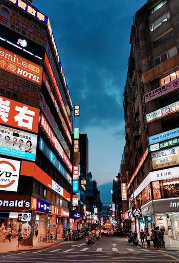 City Architecture Building Exterior Built Structure Sky Street Building Night Advertisement Travel Destinations Illuminated Communication Sign Incidental People Text Road Group Of People Transportation City Life Nature