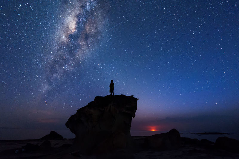 Silhouette Man Standing On Rock Formation Against Star Field At Night