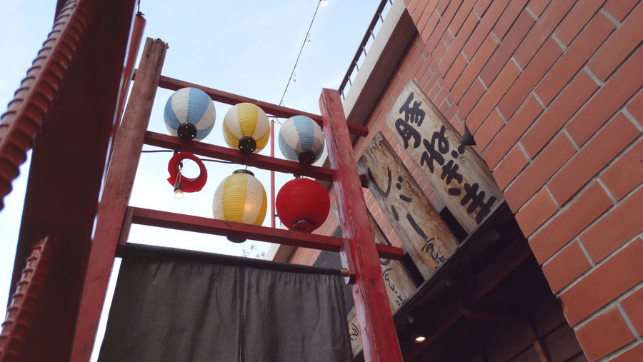 Low angle view of japanese lanterns hanging by brick wall