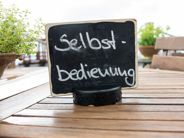 """""""Self service"""" sign on a restaurant table in Germany (""""Selbstbedienung"""" translates to """"Self service"""" in English) Blackboard  Communication Furniture German Language Information No People Outdoors Restaurant Selbstbedienung Self Service Sign Symbol Table Text Text Wooden"""