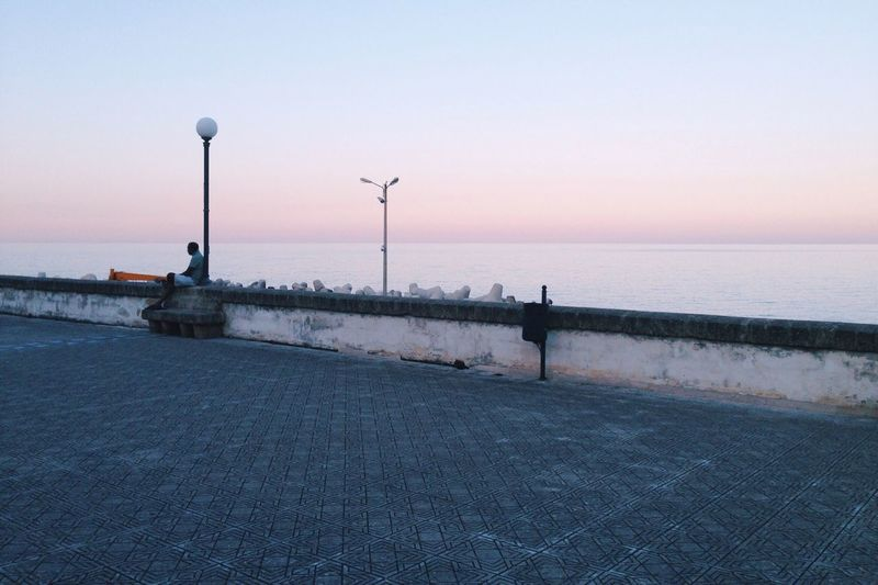 Alone Tranquility Tranquil Scene Sea Dawn Pastel Power Place Village Getting Away From It All Seaside Calm Sky Horizon Over Water Streetphotography Lamp Man Relaxing Empty Places Simple Moment in Italy Lifestyles Pastel Softness Things I Like The Architect - 2016 EyeEm Awards