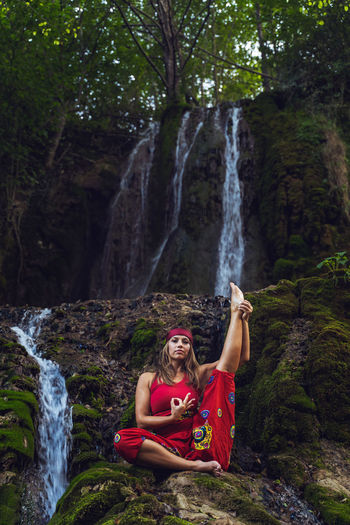 Woman sitting on waterfall in forest