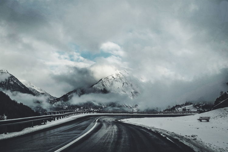 ROAD PASSING THROUGH MOUNTAINS IN WINTER