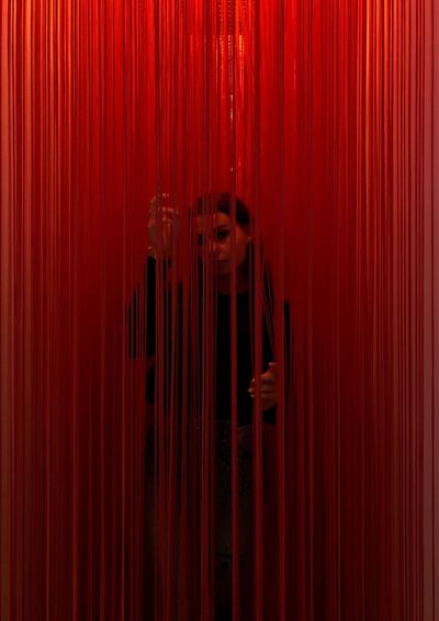Portrait of woman standing amidst red curtain