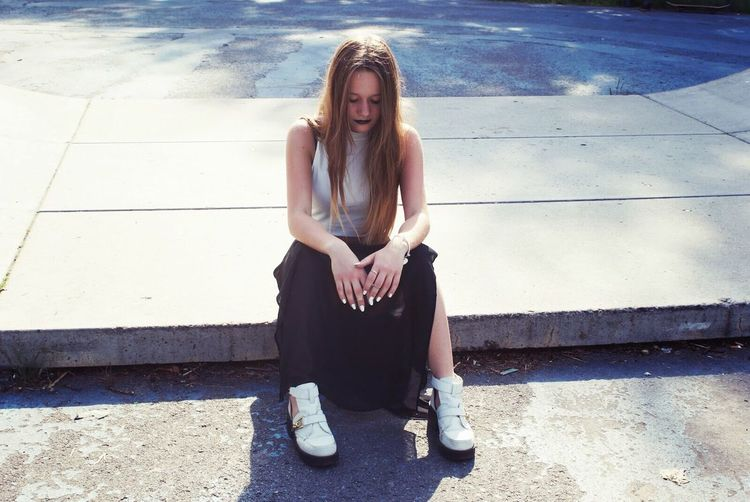 Portrait Of Young Woman Sitting On Skateboard Ramp