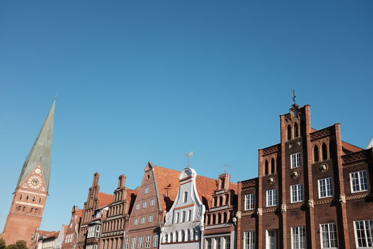 Low angle view of buildings by cathedral against clear blue sky