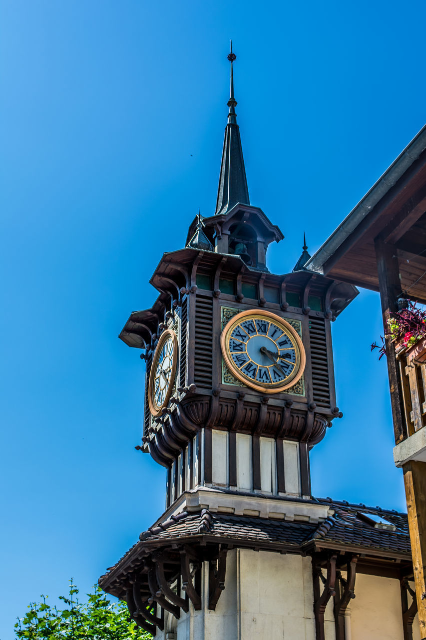 low angle view, architecture, clock, building exterior, built structure, clock tower, time, day, blue, outdoors, flag, clear sky, sky, no people, history, astronomical clock, clock face