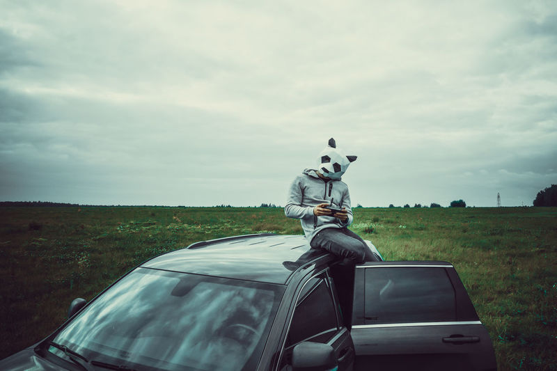 Coin-operated binoculars by car on landscape against sky